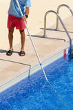Guy cleaning the swimming pool with a telescopic brush Royalty Free Stock Photography