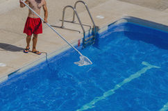 Guy cleaning the swimming pool Stock Photos