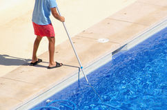 Guy cleaning the swimming pool with a vacuum head Royalty Free Stock Photos