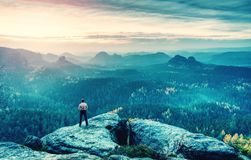 Guy on a cliff above fairy misty valley. Cracked Rock stock photography