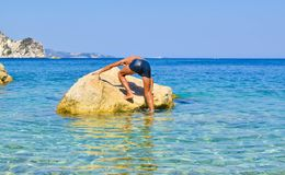 Get on the stone. The guy climbs on thestone in sea royalty free stock photo