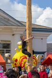 guy climbs on a wooden pole for the prize on the feast maslenitsa day stock photos