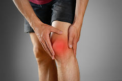 The guy clings to a bad knee. The pain in his leg. Closeup. The. Lesion is highlighted in red Stock Photos