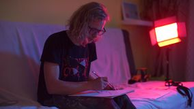 The guy at the club party makes a drawing on paper. A guy with long hair wearing glasses. Sits on the couch at a party in the club, makes a drawing on paper stock video footage