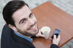 Guy with coffee and mobile phone Royalty Free Stock Photography