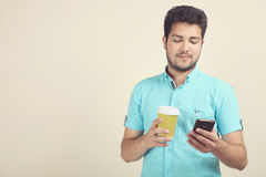 A guy with coffee and a smartphone. Royalty Free Stock Image