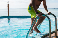 Guy comes out of outdoor pool. Guy in swimming shorts comes out of outdoor pool Stock Photo