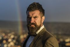 Guy with concentrated face in suit. Hipster with stylish hairdo. In front of sky with rainbow. Barber and hairdo concept. Man with beard and mustache and stock photography