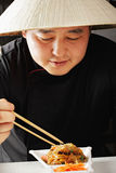 Guy in conical Asian hat having meal Stock Photos