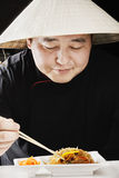 Guy in conical straw hat eating Royalty Free Stock Photo