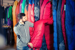 Guy is considering an assortment of sleeping bags Stock Photography