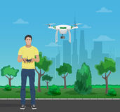 Guy controling aerial quadrocopter drone in the city park. Vector illustration. Royalty Free Stock Photos