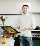 Guy with cooked fish on  frying pan Royalty Free Stock Image