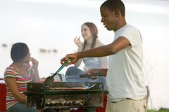 Guy cooking bbq. One happy twenties African American male cooking on a bbq grill outdoors in a park with two friends behind stock image