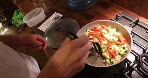 Guy cooking dinner on the kitchen. Young man cooking dinner on the kitchen crop. Sliced zucchini and pepper vegetables on a frying pan stock video footage