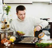 Guy cooking  fish with lemon in baking sheet Stock Photography