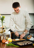 Guy cooking raw fish with  onion in roasting pan. Handsome guy cooking raw fish with  onion in roasting pan at  kitchen Stock Image