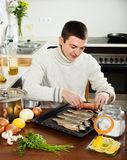 Guy cooking raw fish  in roasting pan Royalty Free Stock Photography