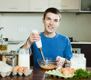Guy cooking scrambled eggs for breakfast Royalty Free Stock Image