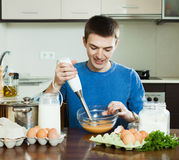 Guy cooking scrambled eggs for breakfast Royalty Free Stock Photography