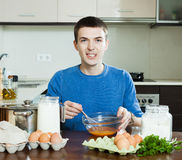 Guy cooking scrambled eggs Royalty Free Stock Image