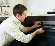 Guy cooking something in the oven Stock Photos