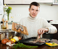 Guy cooking trout fish Stock Photography