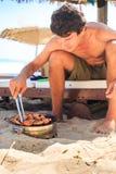 Guy Cooks Chicken Wings en barbacoa en la playa Foto de archivo libre de regalías