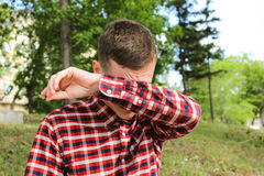 The guy covered his face with his hands, the man cries Stock Photo