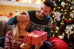Guy covering his girlfriend`s eyes while giving her present. Guy covering his smiling girlfriend`s eyes while giving her present Royalty Free Stock Photo