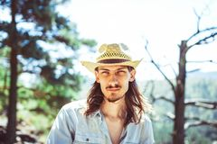 The guy in the cowboy hat. A young man in a cowboy hat against the background of a mountain river Stock Photography