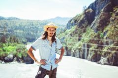 The guy in the cowboy hat. A young man in a cowboy hat against the background of a mountain river Stock Image