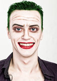 Guy with crazy joker face, green hair and idiotic smike. carnaval costume Stock Photography
