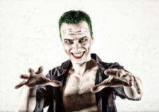 Guy with crazy joker face, green hair and idiotic smike. carnaval costume Royalty Free Stock Images