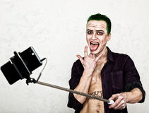 Guy with crazy joker face, green hair and idiotic smile. carnaval costume. making selfy photo Royalty Free Stock Image