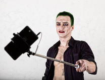 Guy with crazy joker face, green hair and idiotic smile. carnaval costume. making selfy photo Stock Images