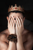 Guy with crown on head covered his face hands. Stock Photos