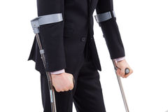 The guy on crutches. Businessman in a suit holding crutches. Isolated on white Royalty Free Stock Photography