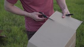 Guy cuts a cardboard box with scissors. the process of assembling a homemade rocket. Close up. Hands and scissors visible stock video footage