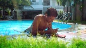 Guy dangles feet in pool water surfing internet over phone. Dark-haired guy dangles feet in pool water surfing internet on phone leaning against resort hotel stock footage