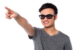 Guy in dark sunglasses pointing at something Stock Image