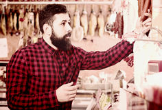 Guy deciding on best sausage. Smiling european guy deciding on best sausage in butcher's shop Stock Photography