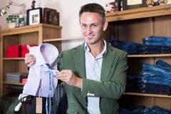 Guy deciding on new shirt. In male cloths store Royalty Free Stock Images