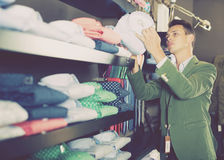 Guy deciding on new shirt. Smiling guy deciding on new shirt in male cloths store Stock Photos