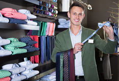 Guy deciding on new tie. Happy guy deciding on new tie in male cloths store Royalty Free Stock Photography