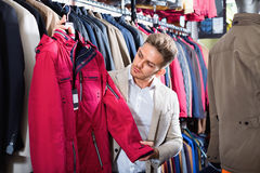 Guy deciding on warm coat in men's cloths store Royalty Free Stock Image