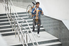 Guy in denim jacket going down the stairs holding an orange bicycle. Student with the bike. Going down Royalty Free Stock Images