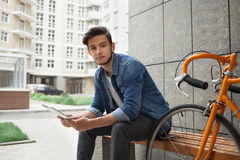 Guy in denim jacket, tablet and orange bicycle Royalty Free Stock Photos