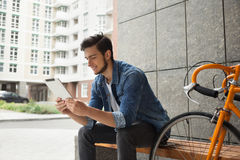 Guy in denim jacket, tablet and orange bicycle Stock Photo