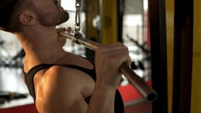 Guy with developed muscles doing pulldown exercise, workout in gym, endurance. Stock photo stock photos
